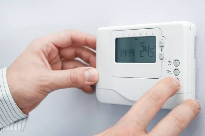 uomo che accende un termostato ambiente